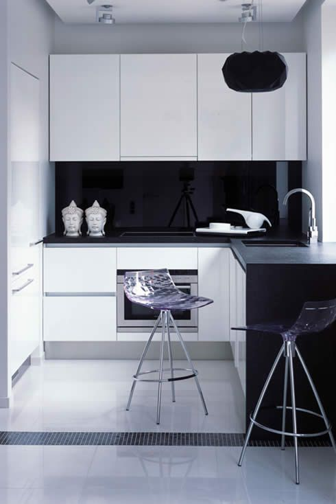 tiny kitchen with a glossy black backsplash and transparent stools