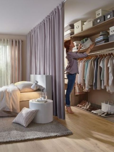 a dusty pink space divider not only adds to the girlish bedroom decor but also separates the bedroom and the closet