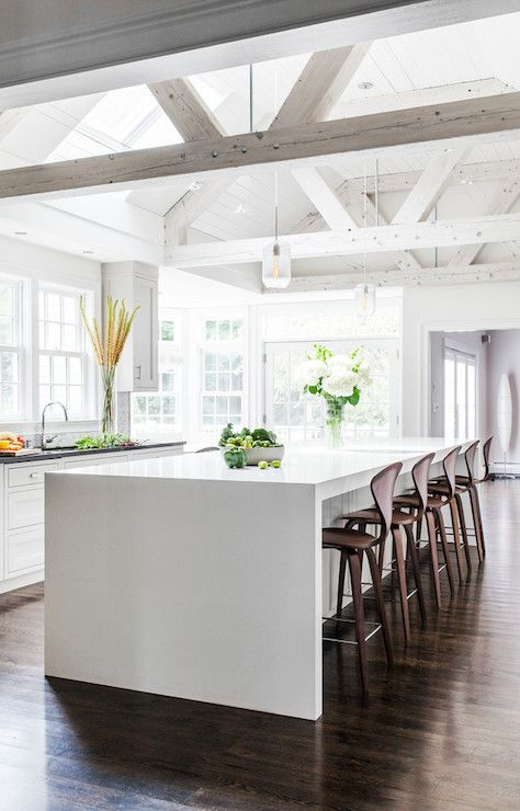 rustic kitchen design is modernized with a sleek white waterfall countertop