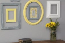 25 cream, grey and yellow frames on a light grey wall