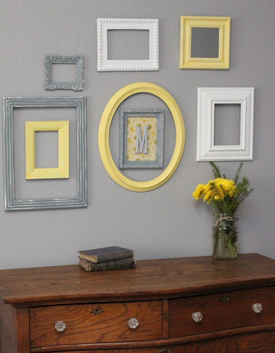 cream, grey and yellow frames on a light grey wall