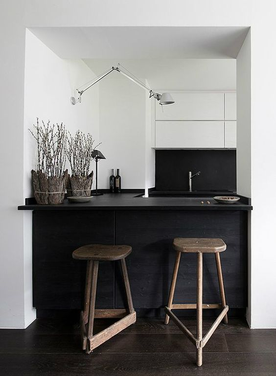 small minimal black and white kitchen with a kitchen island and dining space in one