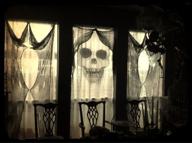use black cheese cloth as spooky yet classy curtains for Halloween decorations