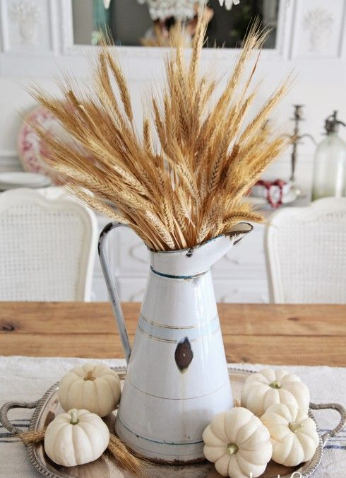 centerpiece with small pumpkins and wheat in a metal pitcher