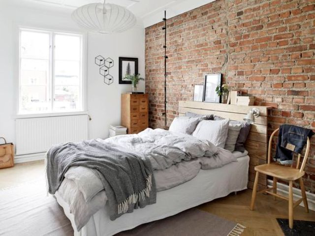 vitnage-inspired bedroom is accentuated with an exposed brick wall