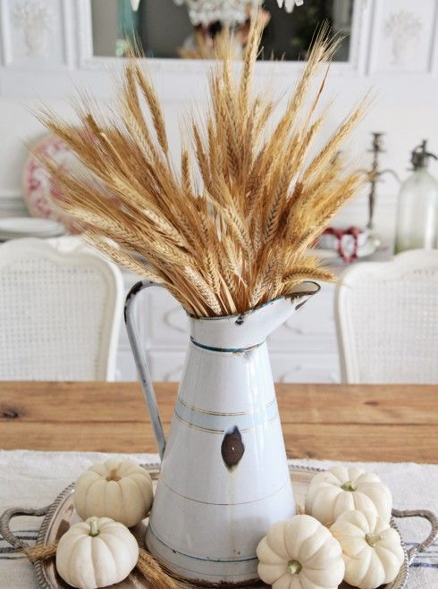 harvest centerpiece with white pumpkins and wheat in a vintage pitcher