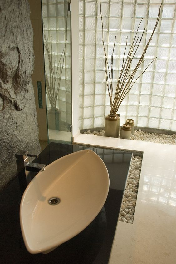 rough stone wall and pebbles on the floor give an Asian feel to this bathroom