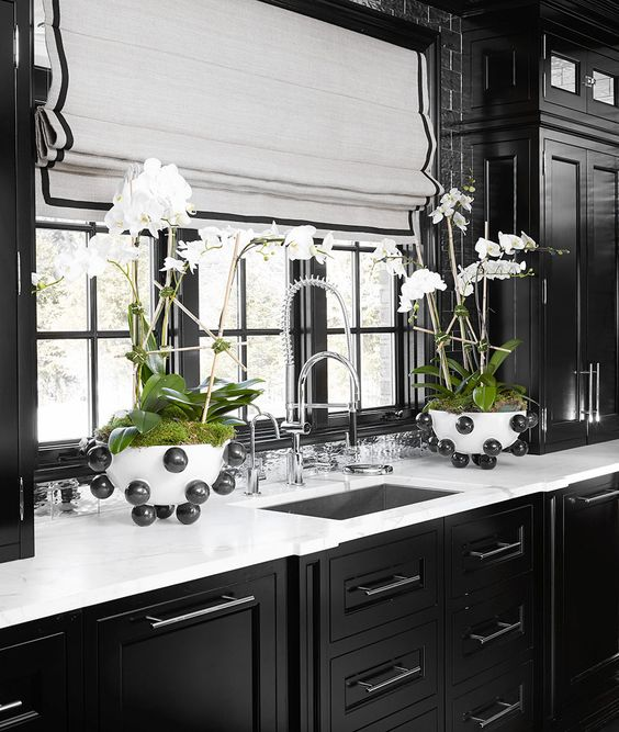 orchids in moss add a luxurious touch to this traditional dark moody kitchen