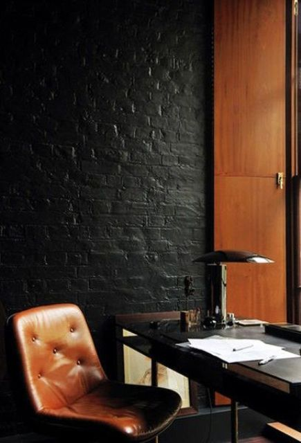 mid-century modern office with warm woods and leather is accentuated with a black brick wall