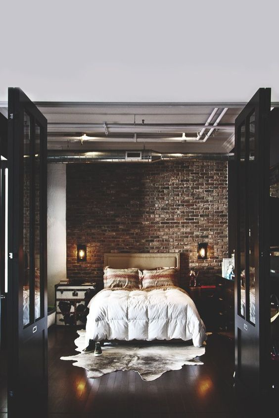chic moody bedroom becomes luxurious thanks to the dark bricks