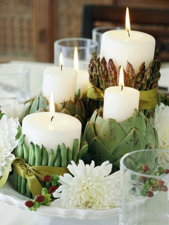 dish centerpiece with candles covered with artichokes, asparagus and peas