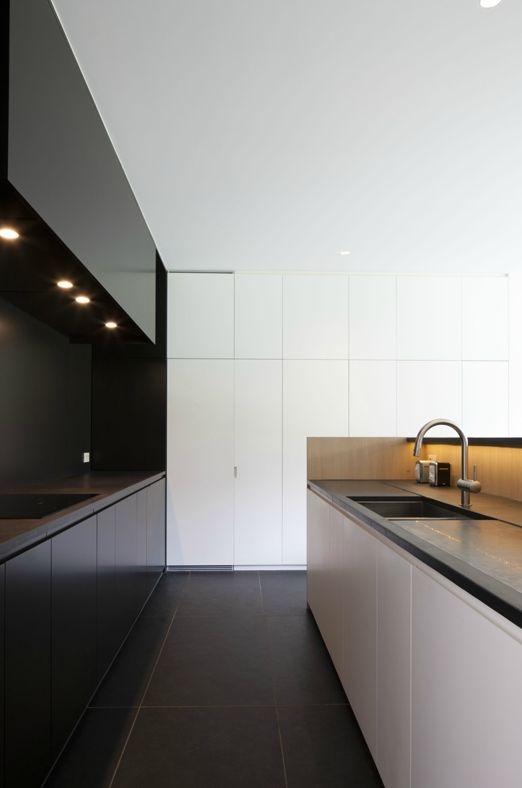 kitchen with a white and a black half and lights to keep the space luminous