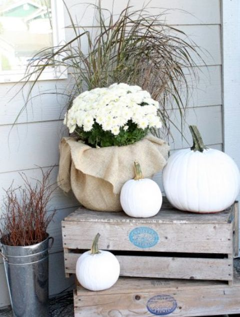 outdoor crate display with white pumpkins and potted flowers
