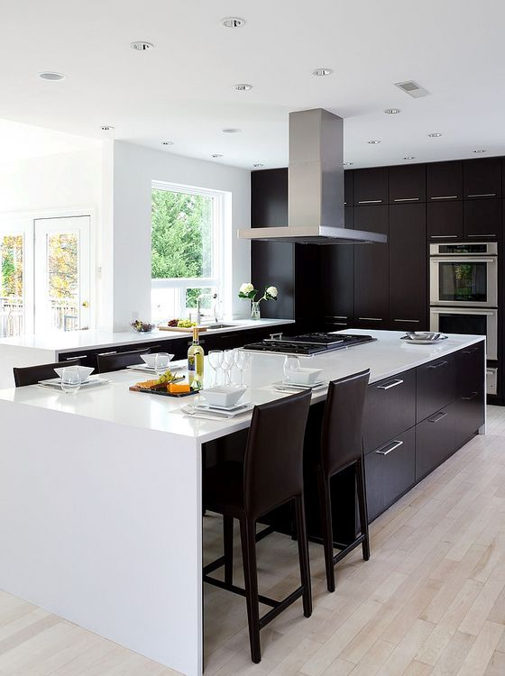 modern black and white kitchen with light-colored wooden floors and a steel hood
