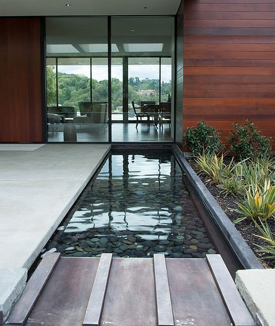 simple and stylish water feature mirrors the contemporary glass facade beautifully