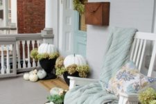 35 white pumpkins, a white rocker and a pastel blanket and pillow