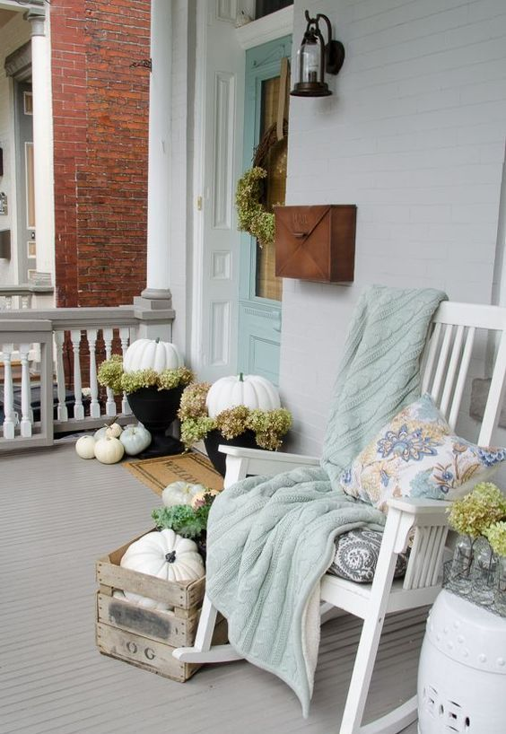 white pumpkins, a white rocker and a pastel blanket and pillow