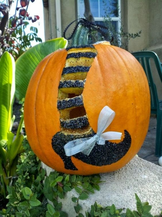 Picture Of Witch Leg With Glitter And A Bow On A Pumpkin