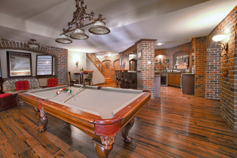 a game room and a bar are perfect additions to any basement and brick walls are a must there for a cool industrial vibe (M.J. Whelan Construction)