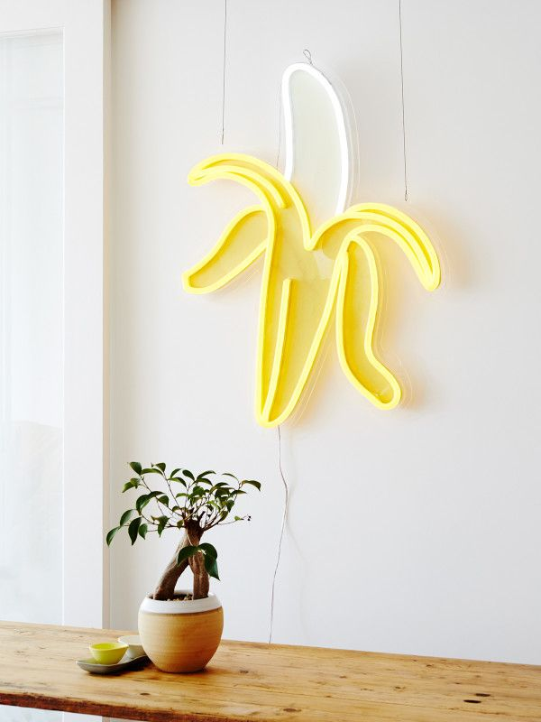 A banana neon light would shine on a neutral gray wall.