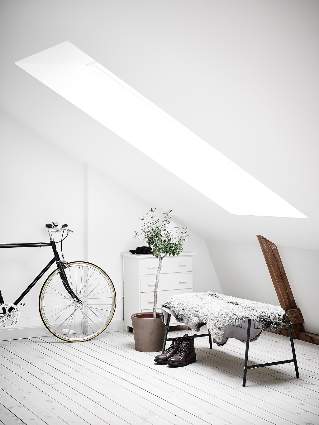 The entryway is filled with light through the attic window, the bench is covered with fur for comfort