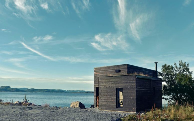 This dark wooden cabin is located on a northern coast, and it features Scandinavian design with some coastal touches