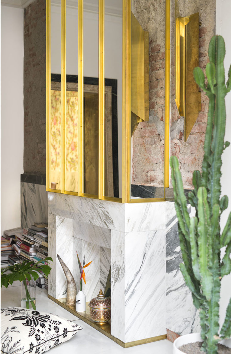 Carrara marble is one of the luxurious materials used throughout the house, and it works well with a gilded framed mirror