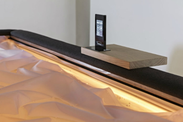 The piece has a comfy caddy for gadgets and lights that remind of bathtubs filled with water