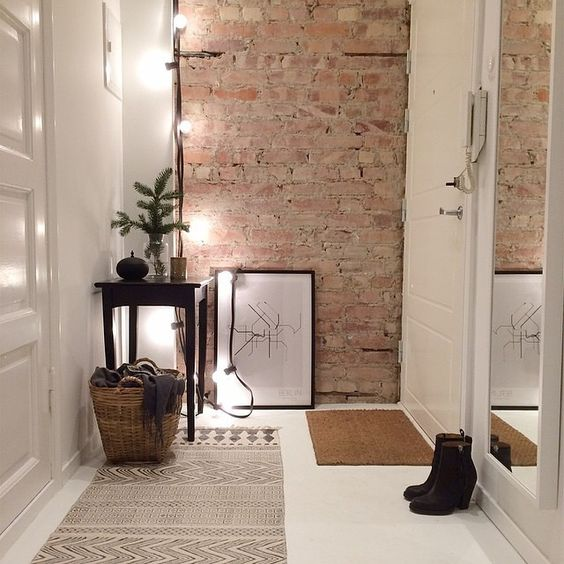 small decluttered entryway with an exposed brick wall, lights and a tall mirror
