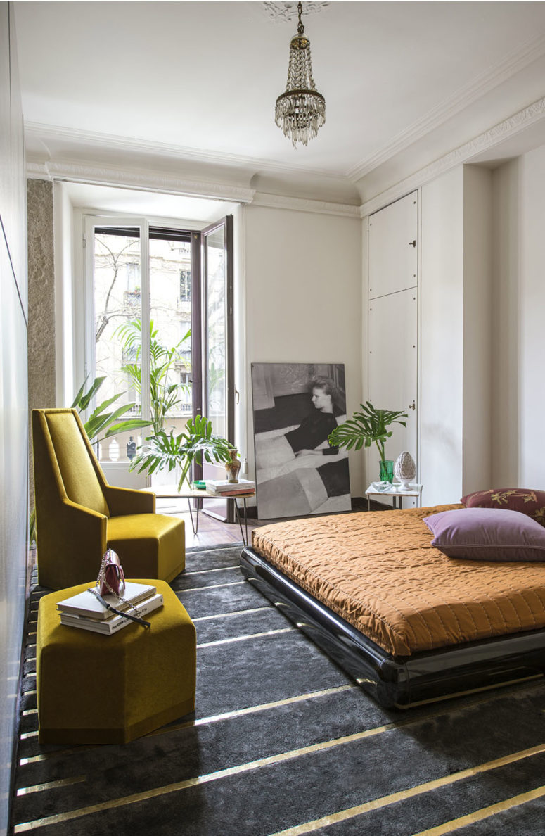 The bedroom surprises with geometric furniture, a sleek black bed on the floor and bold textiles