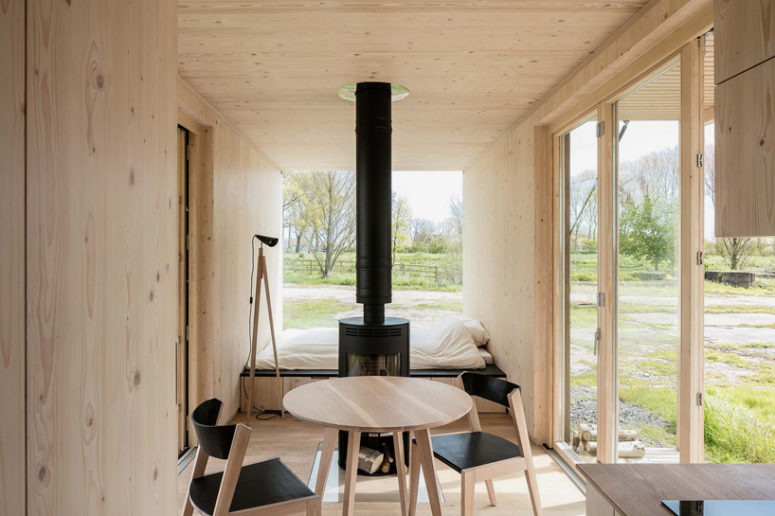 The inside is clad with light-colored warm woods to make it natural and cozy, and the furniture is contrasting black