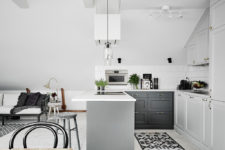 03 The kitchen is modern, with grey and white cabinets and greenery to enliven the look