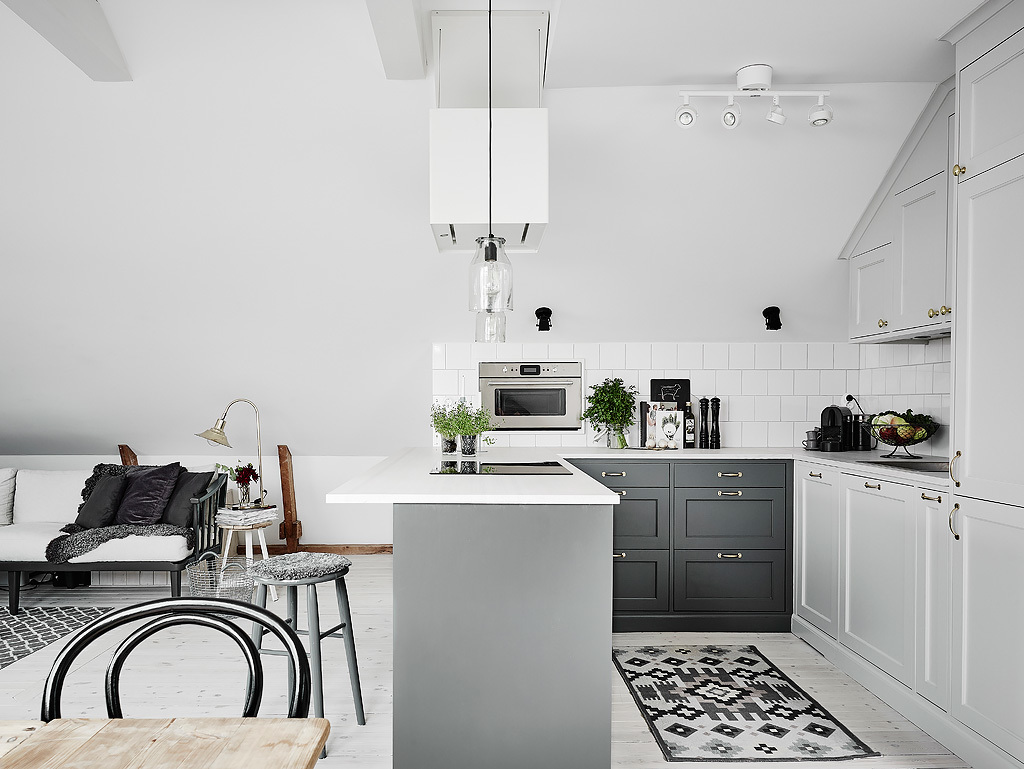 The kitchen is modern, with grey and white cabinets and greenery to enliven the look
