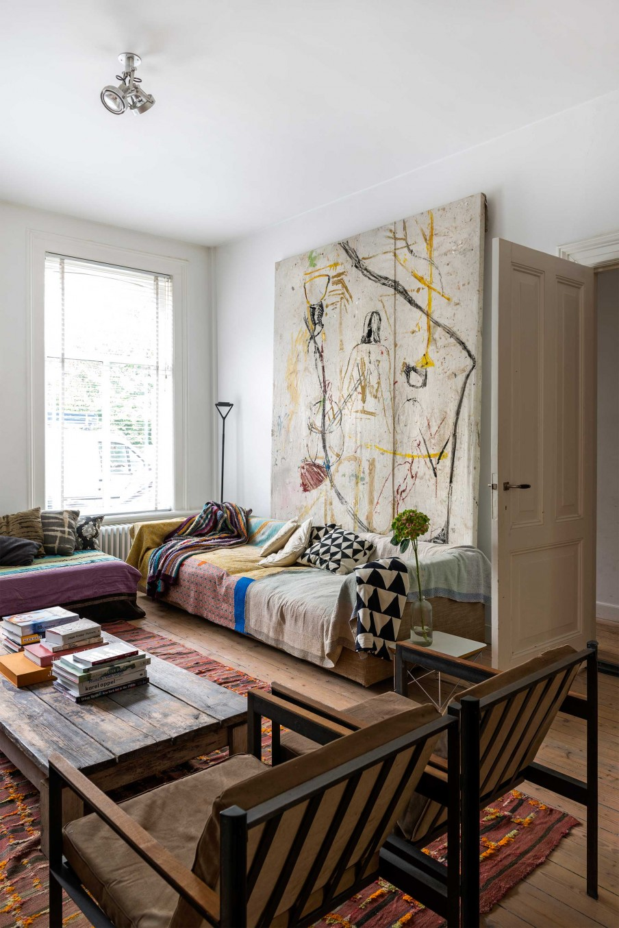 The living room has leather chairs, artworks of the owner and bold boho textiles, it's eclectic