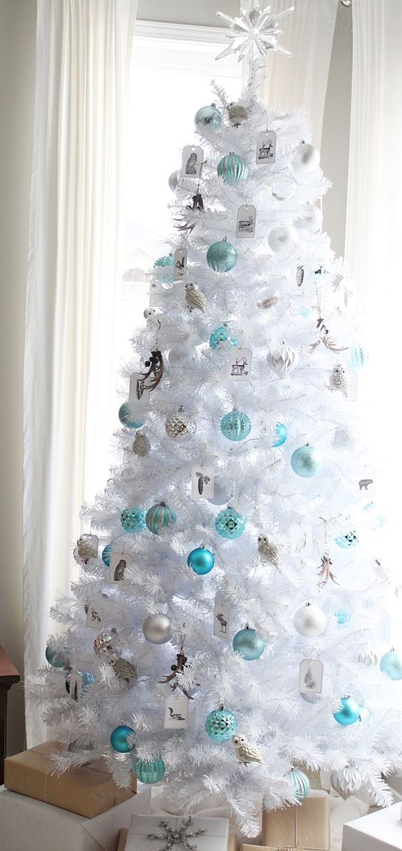 crispy white christmas tree decorated in blue and silver breathes with frost
