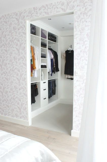very small walk in closet in white with a leading rack on the left wall - Small Walk In Closet Design Ideas