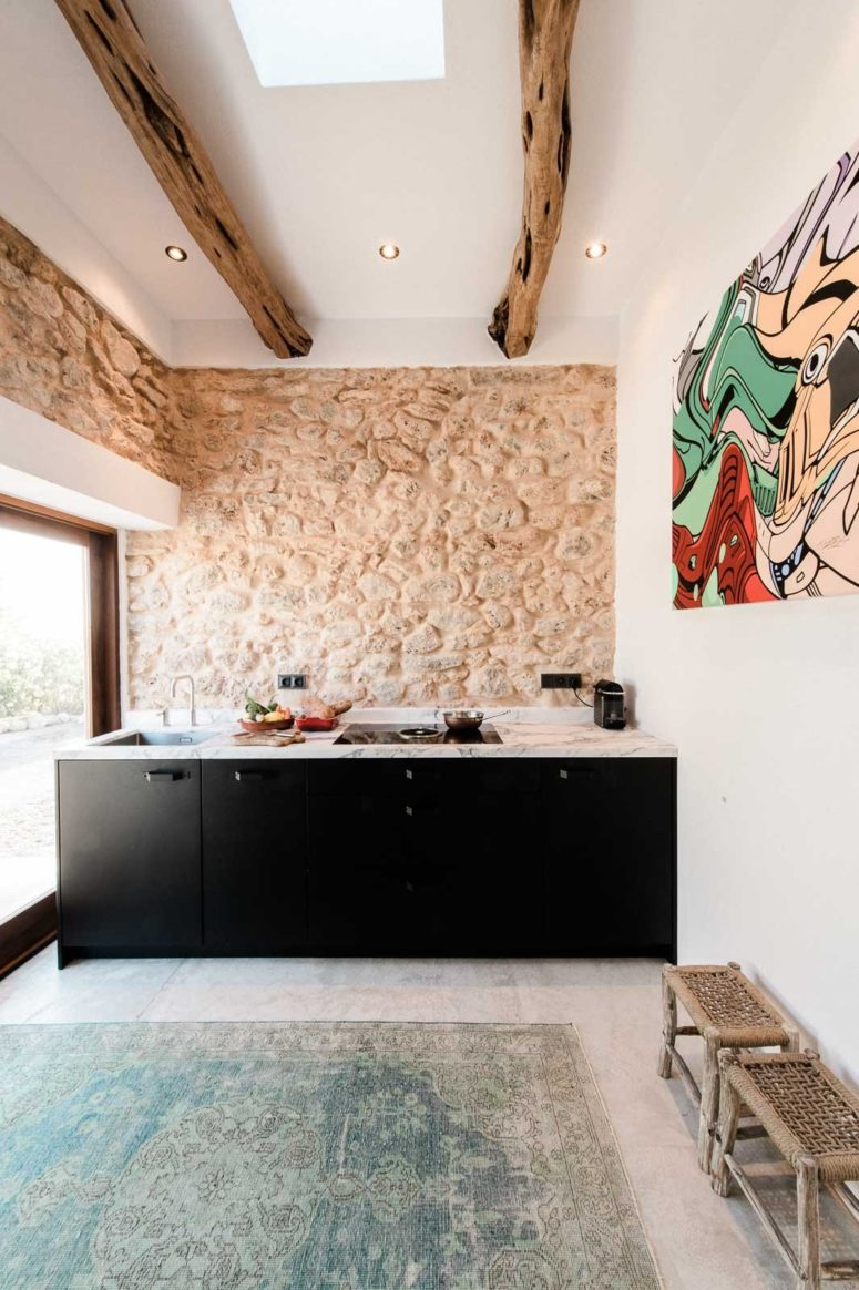 The kitchen features original stone clad used as a backsplash and original exposed wooden beams yet minimalist furniture