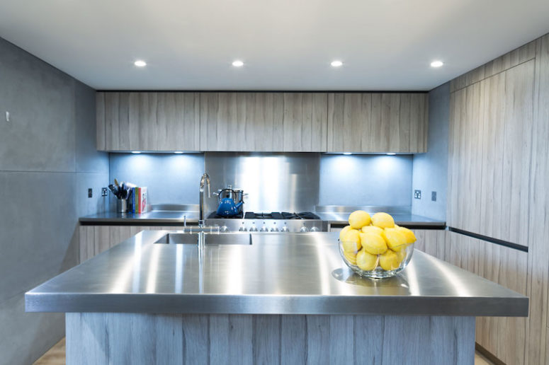 The kitchen is decorated in light grey, concrete and stainless steel, there are a lot of lights