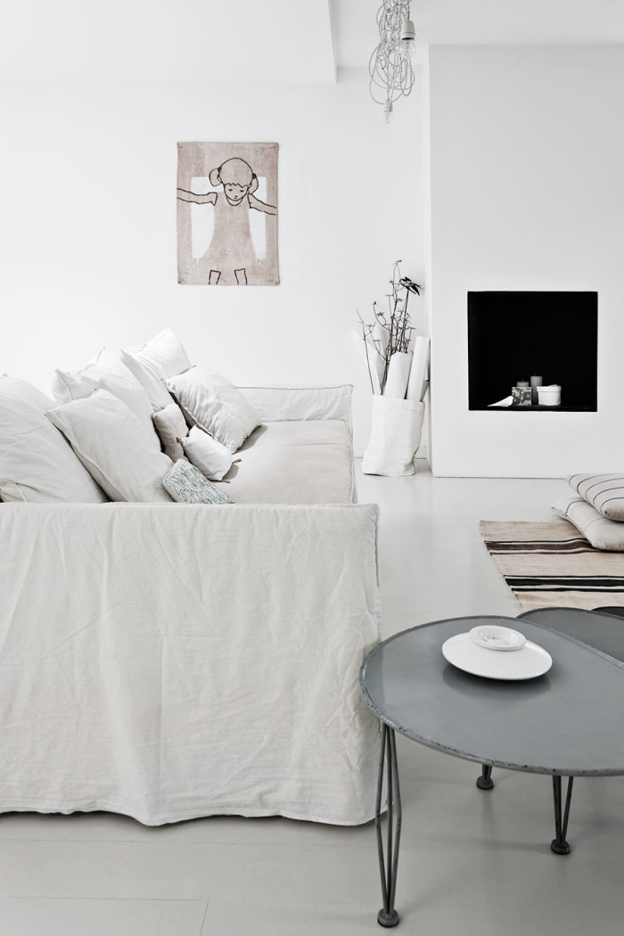 The living room is Scandi classics, with a faux fireplace, rough white textiles and even burlap