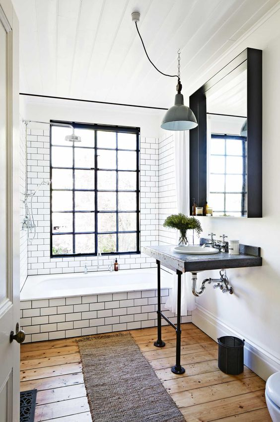 Industrial And Mid Century Modern Bathroom With Subway Tiles On The Walls  And Bathtub