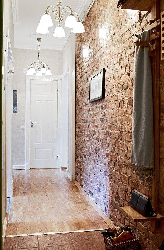 narrow entryway with a brick wall that adds texture
