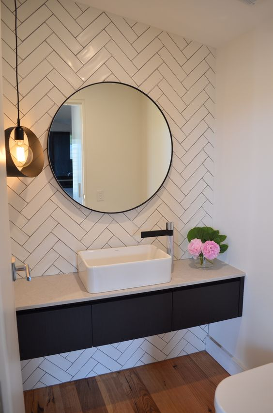 white subway tiles clad in herringbone pattern in the bathroom