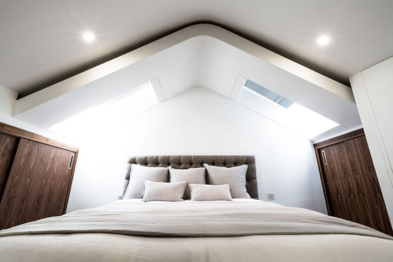 The bedroom features an attic roof with windows and a mix of chocolate brown and white