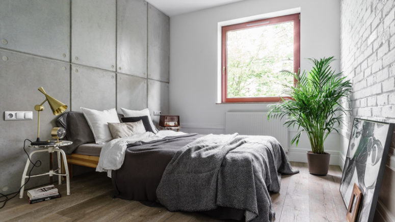 The bedroom is covered with concrete and brick panels, and potted greenery enliven the greyish space