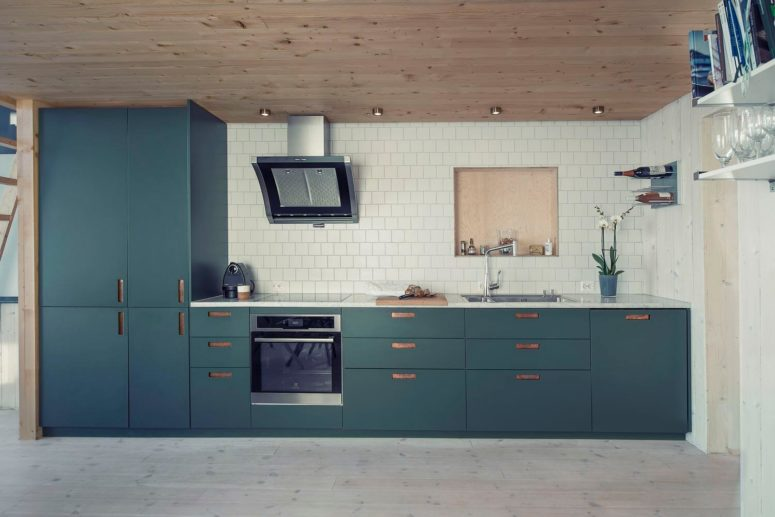 The kitchen has modern blue cabinets and drawers, a cool warm wooden ceiling and a whitewashed floor