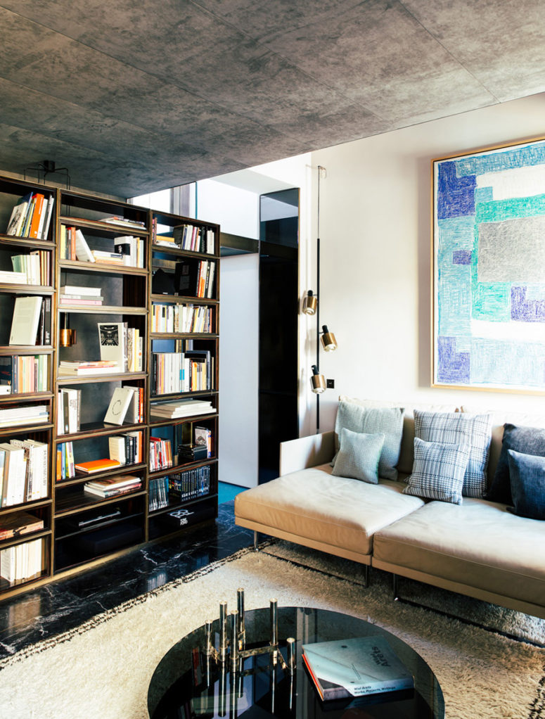 The living room is lighter and fresher, black marble on the floor, beige textiles and blue accents look chic and welcoming