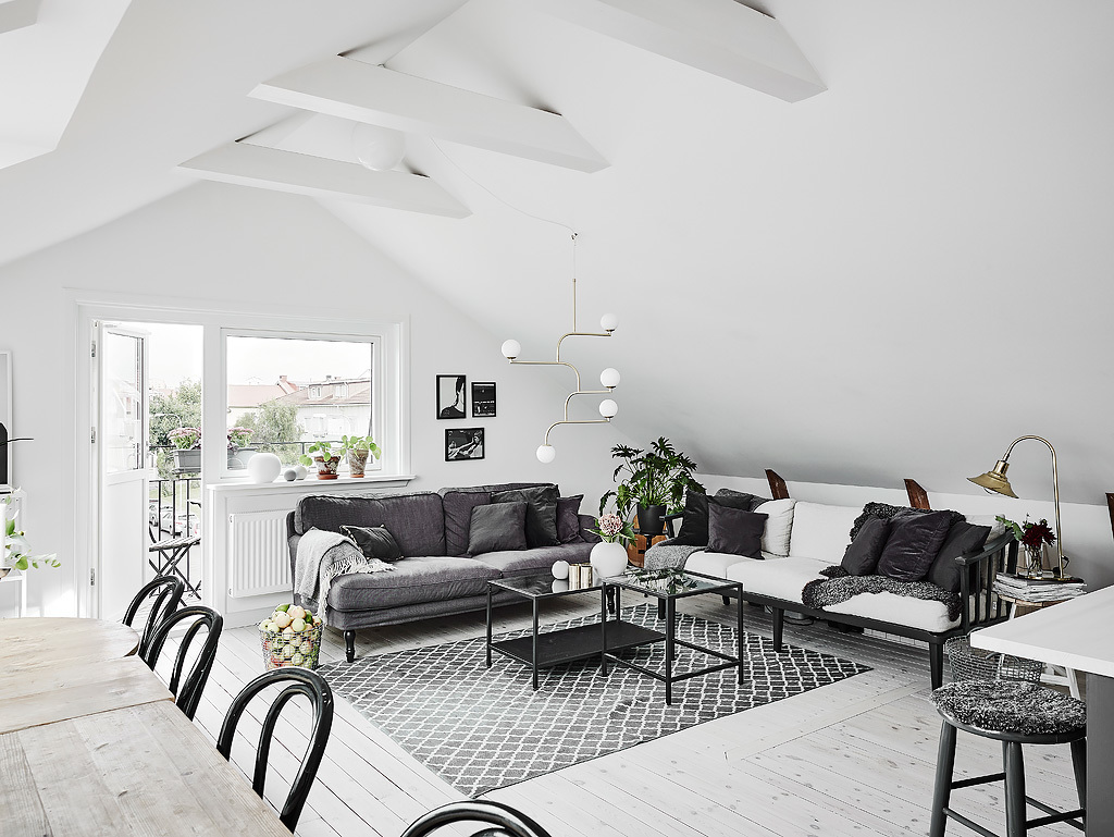 The living space features two sofas in grey and white, mid century modern lamps and textiles bring coziness