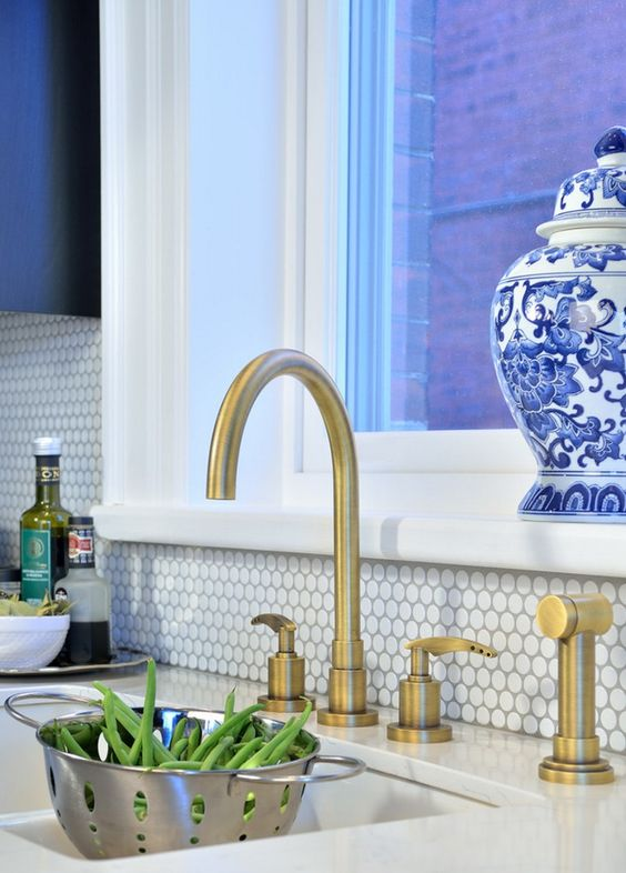 kitchen with white penny tiles and brass faucets