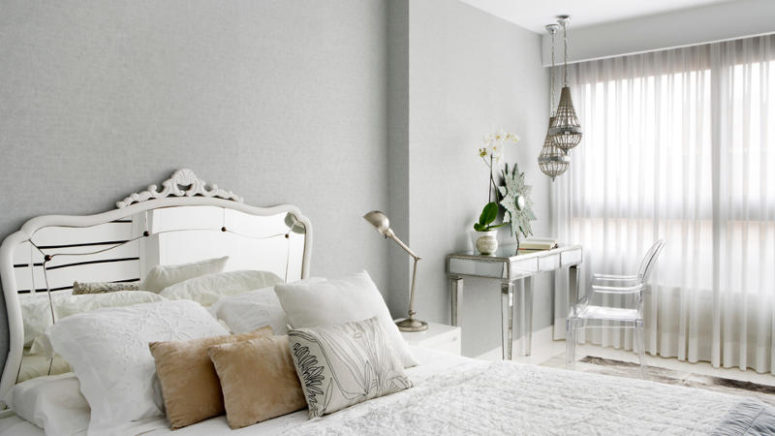 The bedroom is glam, with a mirrored bed and table and a cool lucite chair