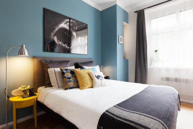 The bedroom itself is done in grey and accentuated with yellow and a blue headboard wall